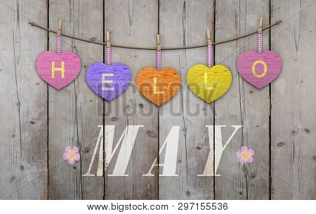 Hello May Written On Hanging Pink And Orange And Purple Hearts And Weathered Wooden Background, With