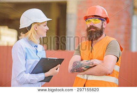 Woman Inspector And Bearded Brutal Builder Discuss Construction Progress. Construction Project Inspe
