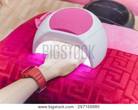 Hand Of Woman Drying Her Nails In Pink Uv Lamp On Magenta Color Pillow. Professional Manicure In Sal