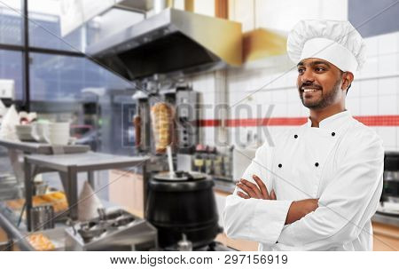 cooking, profession and people concept - happy male indian chef in toque over kebab shop kitchen background