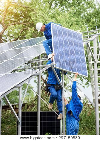 Installing Of Stand-alone Solar Photo Voltaic Panel System. Workers In Hard-hats And Blue Overall Li