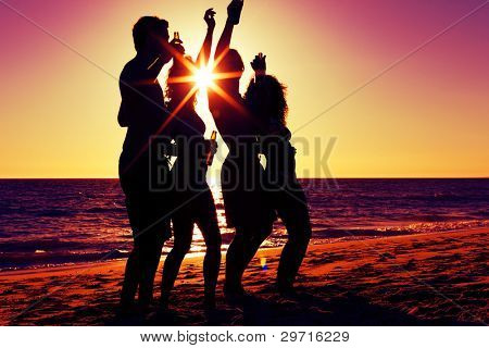 People (two couples) on the beach having party, drinking and having a lot of fun in the sunset (only silhouette of people to be seen, people having bottles in their hands with the sun shining through)