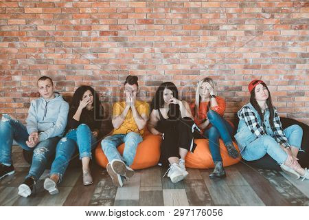 Empathy And Compassion. Group Of Close Friends Sitting On Bean Bags With Sad Facial Expressions. Fee