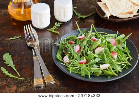 Salad Of Fresh Vegetables - Arugula, Radish, Feta Cheese In Black Plate With Flat Bread Tortilla. He