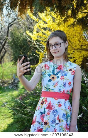 Portrait Of Beautiful Girl With Glasses And Brown Hair Making Selfie On Smart Phone. Young Smiling T