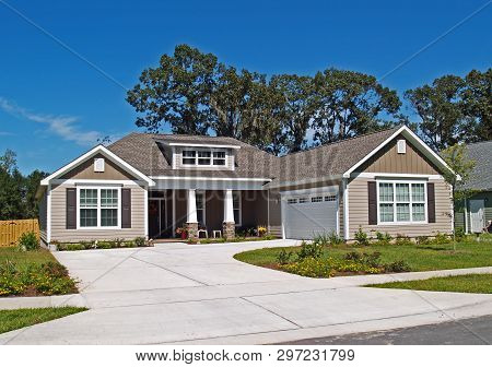 Single Story Home With Garage And Tan Siding.
