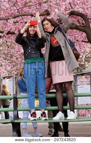 Stockholm, Sweden - April 22, 2019: Two Young Women Standing On A Green Bench In The Kungstradgarden