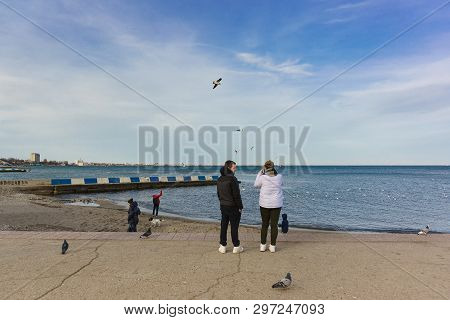 Feodosia, Crimea, Russia - March 08, 2019: Vacationers Walk On The Waterfront Resort Town In The Off