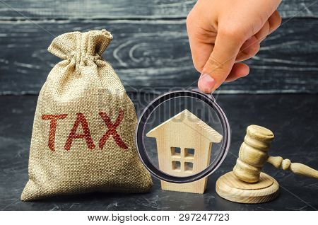 A Bag With Money And The Word Tax Next To A Wooden House. Taxes On Real Estate, Payment. Penalty, Ar