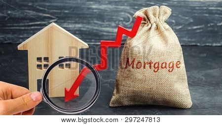 Bag With The Money And The Word Mortgage And Arrow To Down And House. Low Interest In Mortgages. Red