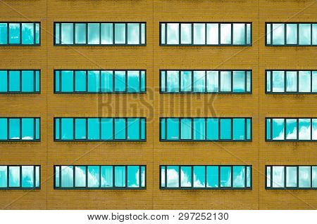 Yellow Brick Wall With Windows. Facade Of Office Building With Windows. Facade Of An Old Yellow Bric