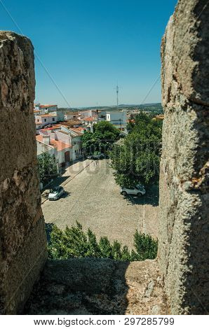 Old Houses And Cobblestone Street On Sunny Day, Seen From Crenel In The Wall Of Elvas Castle. A Grac