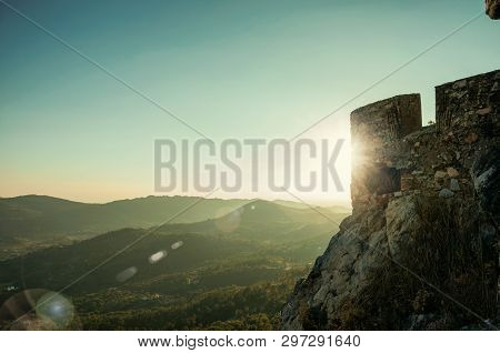 Stone Wall With Merlons In Castle Over Hill On Sundown, With Mountainous Landscape At Marvao. An Ama