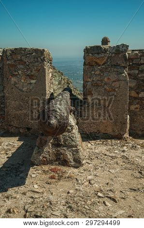 Close-up Of Old Iron Cannon Aiming Through Crenel In The Stone Inner Wall, In A Sunny Day At The Mar