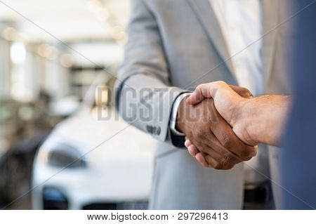 Closeup of a salesman shaking hands with his client after selling him a car at the dealership. Handshake between customer and african car dealer at automobile showroom.