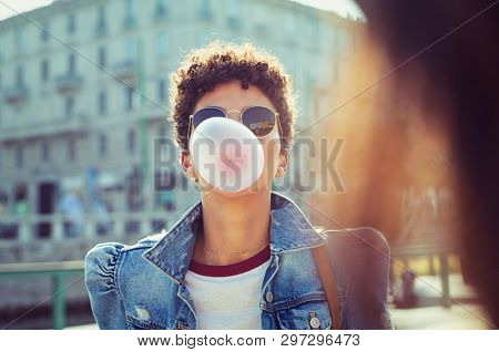 Young african girl in sunglasses with curly hair puffs bubble of chewing gum in city street. Brazilian young woman inflates pink chewing gum. Stylish woman making bubblegum of chewing gum.