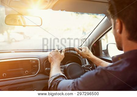 Rear view of young man looking straight while driving a car. Business man driving on the road. Back view of guy in formal clothing sitting on driver seat. Traveling for business work.