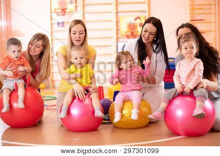 Group Of Young Mothers And Their Babies Doing Yoga Exercises On Gymnastic Balls At Fitness Gym