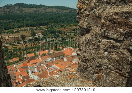 Cityscape With Old House Roofs And Hilly Landscape, Seen By Crenel In The Castle Wall At Castelo De