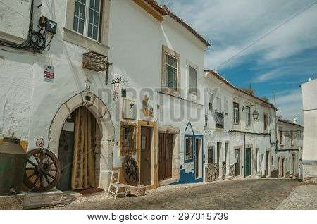 Estremoz, Portugal - July 06, 2018. Old houses with doors on alley with cobblestone pavement in sunny day at Estremoz. A nice little historic town with several marble buildings on eastern Portugal.