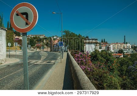 Portalegre, Portugal - July 08, 2018. Road Sign In Street With Breastwork, Flowered Bushes And Build