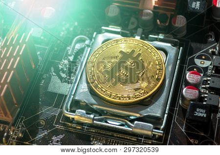Golden physycal bitcoin among the electronic computer elements. Business concept of digital bitcoin cryptocurrency. Blockchain technology and bitcoin mining concept