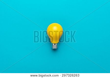 Flat Lay Photo Of Yellow Bulb On Turquoise Blue Backgound. Top View Of Lightbulb In The Center Of Th