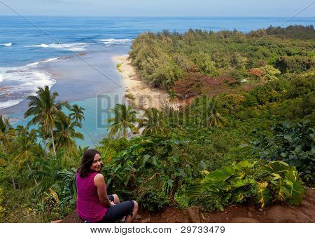 Female hiker overlooking Kee beach from Kalalau trail on Na Pali coast of Kauai poster