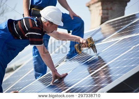Male Engineers Installing Stand-alone Solar Photovoltaic Panel System Using Screwdriver. Electrician