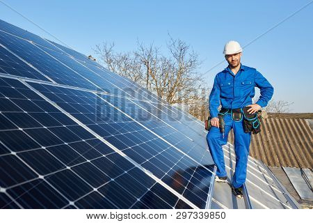 Smiling Engineer In Blue Suit And Protective Helmet Installing Solar Photovoltaic Panel System Using