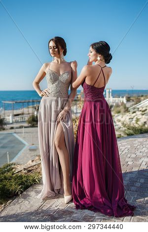 Two Sisters In Elegant Evening Dress.  Girls With Long Healthy And Shiny Hair. Beautiful Young Woman