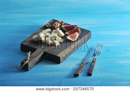 Cheese With Blue Mold Dorblu On A Wooden Board. To Shade The Taste Of Cheese Added Slices Of Ripe Fi