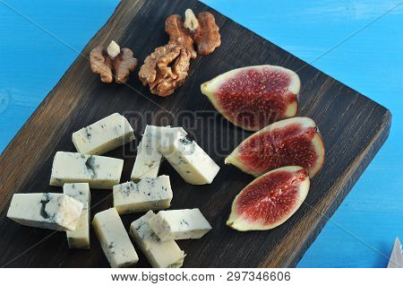 On A Wooden Board, Cheese With Blue Mold Dorblu, A Few Figs And Walnuts. Blue Wood Background. Close
