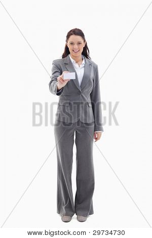 Smiling businesswoman smiling showing a card against white background
