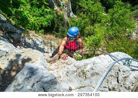Adventurous, Courageous Woman Climber On A Via Ferrata Route Called Casa Zmeului, A Popular Tourist
