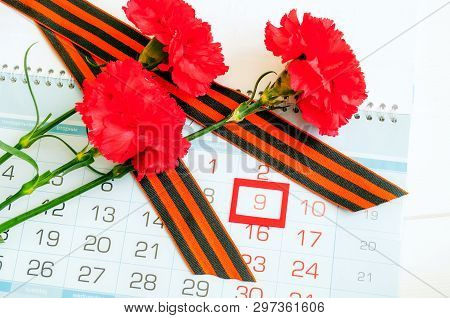 9 May - red carnations and George ribbon lying on the calendar with framed 9 May date, festive 9 May card. 9 May victory day background