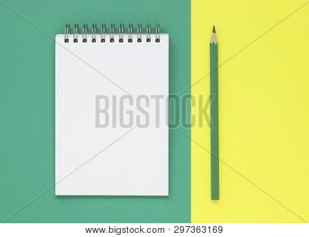 Open Blank Notepad With A Green Pencil, On A Green And Yellow Flat Lay Background. With Copy Space.