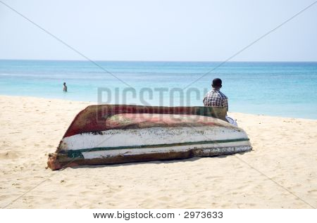 A Man Sitting On Upturned Boat On Stunning Beach.
