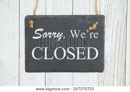 Sorry We're Closed Text On A Hanging Chalkboard On Weathered Whitewash Textured Wood