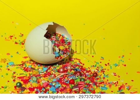 Multicolored Candy Sweets On Yellow Background. Closeup Of Multicolored Small Candies In The Eggshell. Minimal Art Design. Desserts, Holidays, Birthday Concept. Broken Eggs And Colorful Candies. poster