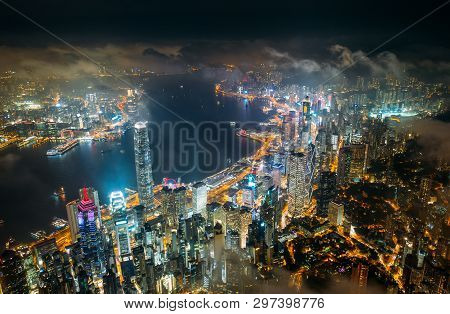 Aerial View Of Hong Kong City Skyline At Night Over The Clouds