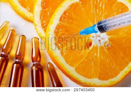 Vitamin C, Natural Anti Aging Cosmetics Serum And Syringe With Ornge Fruit Slices