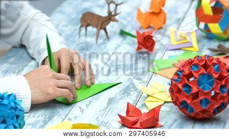 Man At Origami Folding Lesson. Collection Of Beautiful Origami Figurines On Wooden Table. Traditiona