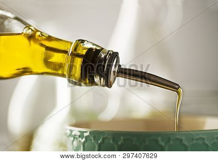 Cooking Meal With Oil. Bottle Of Extra Virgin Oil Pouring In To Bowl For Preparing A Meal. Healthy F