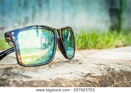 Fashionable Sunglasses. Sunglasses With Mirrored Lenses. Reflection Of The Beach And Tropical Palm T