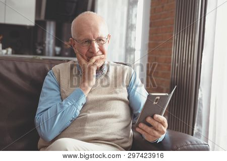 Senior Man Using A Smartphone And Smiling While Sitting On Couch At Home.