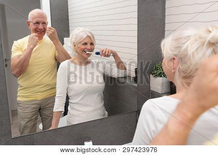 Old Senior People Cleaning Teeth In The Bathroom