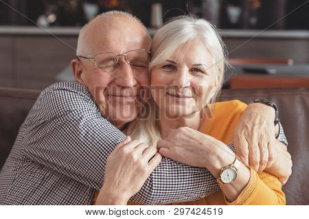 Cheerful Senior Couple Hugging On Sofa At Home