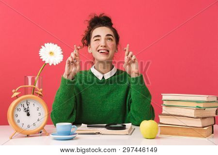 Funny young nerd student girl pointing and looking up while sitting by the table over pink background