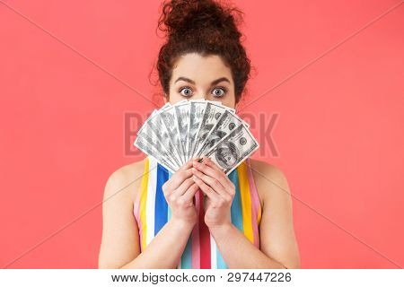 Playful pretty redhead woman wearing in dress hiding behind money and looking at the camera over pink ackground